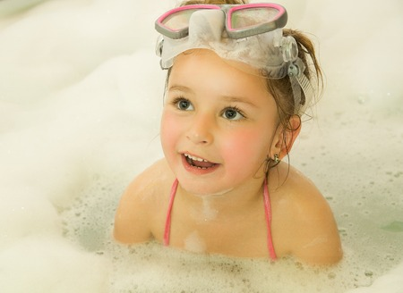 little beautiful girl playing with water and foam in bath using a swimsuit and beautiful dive sunglasses Stock Photo
