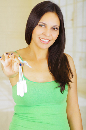 Young beautiful woman with a green blouse holding a menstruation cotton tampon, pointing in front of her Stock Photo