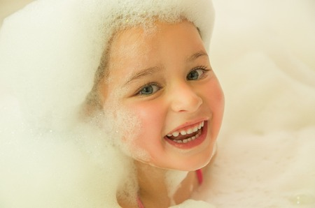 A happy smiling little beautiful girl playing with water and foam in bath Stock Photo