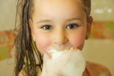 klein mooi meisje spelen met water en schuim met haar mond in bad