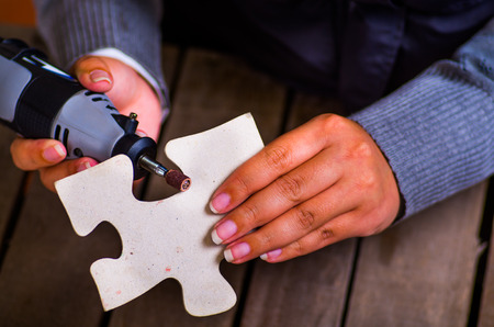 hardworker: A closeup of a hardworker woman using a polisher over a gray puzzle piece on a wooden background Stock Photo