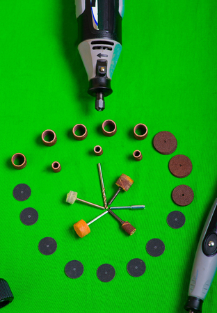 cutter: A gray drill with drilling accessories on green background aerial view Stock Photo