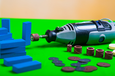 A gray drill with some drilling accessories with a small blue wooden pieces on a green background Stock Photo