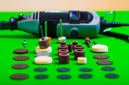 A gray drill behind of the drilling accessories on green background