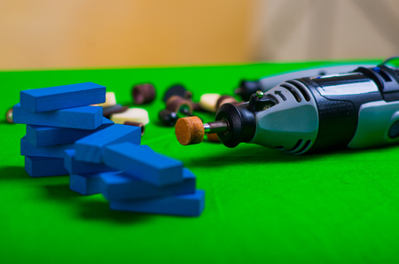 A gray drill with a small blue wooden pieces on a green background Stock Photo