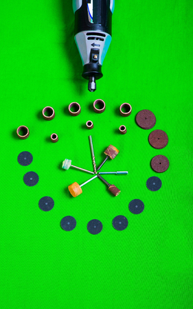 A gray drill with drilling accessories on green background aerial view Stock Photo