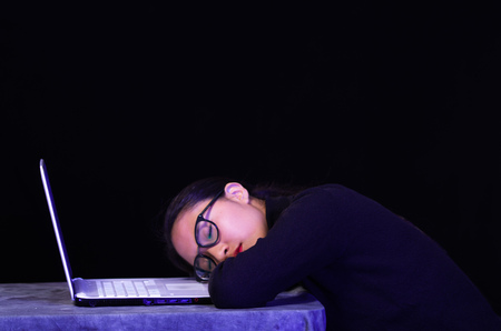 Beautiful girl fell asleep over her laptop wearing her glasses on dark background
