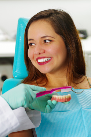 dentalcare: Beautiful woman patient smiling while the doctor is brushing a fake dental plaque in a dentists office Stock Photo