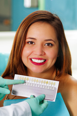 Beautiful woman patient having dental treatment at dentists office while he is holding a dental Vita Shade Guide Classical For Whitening And Bleaching