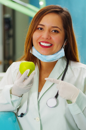 dentalcare: Beautiful woman patient with a stethoscope around her neck is holding a delicious apple in a dentists office