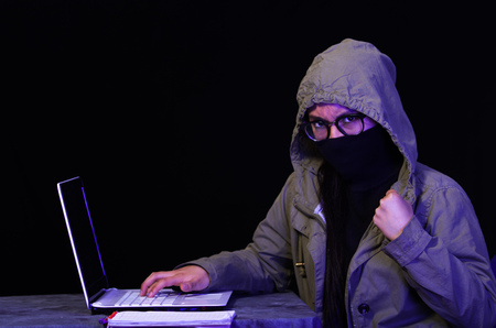 Portrait of a beautiful and smart girl hacker with laptop on dark background using glasses and covering her neck, mouth and nose with her turtleneck sweater and covering her head with a jacket Stock Photo
