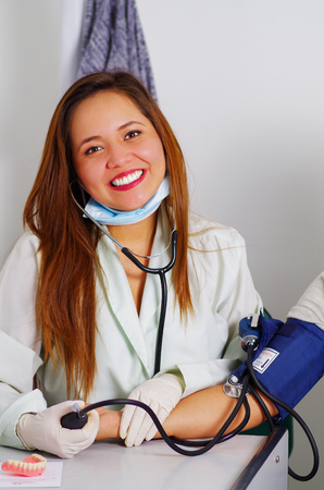 dentalcare: Beautiful doctor woman takes a patients pressure in at dentists office