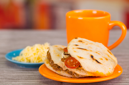 Traditional delicious arepas, shredded chicken avocado and cheddar cheese and shredded beef with a orange cup on wooden blackground