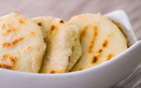 Close up of a traditional delicious arepas, shredded chicken avocado and cheddar cheese and shredded beef on wooden background