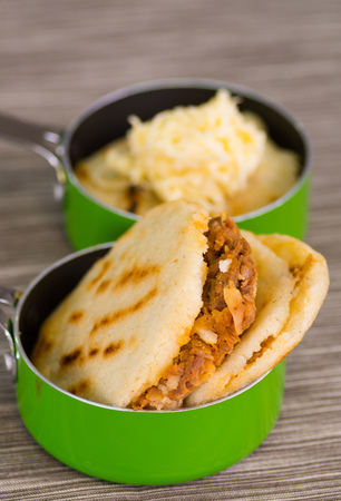 Traditional delicious arepas, shredded chicken avocado and cheddar cheese and shredded beef inside of green saucepan over wooden blackground