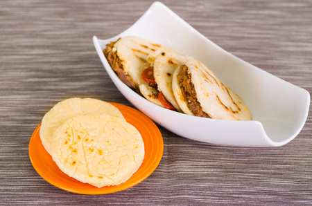 Traditional delicious arepas, shredded chicken avocado and cheddar cheese and shredded beef on wooden background