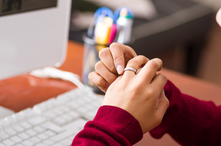 Hands holding a ring in an office, anxiety concept