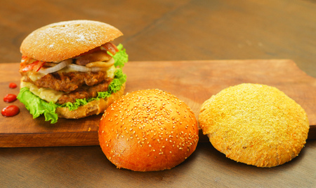 Delicious complete hamburger with two pieces of bread next to the hamburger on wooden board