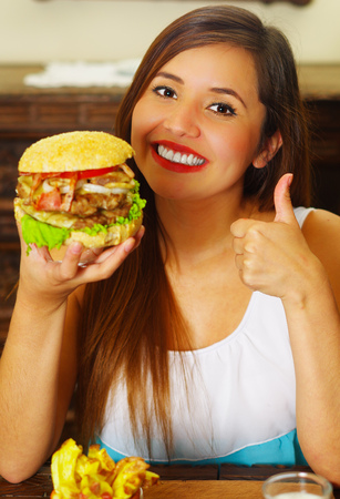 beauty woman in cafe approving a delicious hamburger with a thumbs up