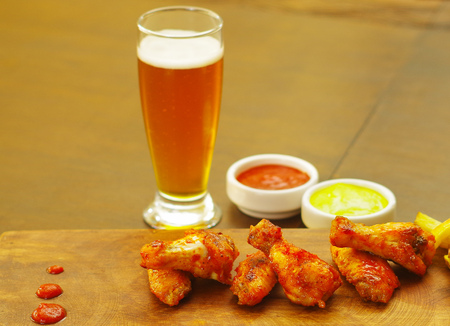 broiling: Delicious grilled chicken wings with ketchup, mustard and a glass of beer on wooden board