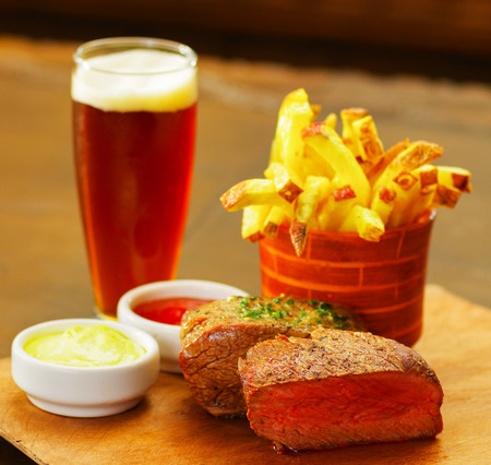 broiling: Close up of a well-done grilled marinated beef flank steak with ketchup, mustard and french fries with a glass of beer on wooden board