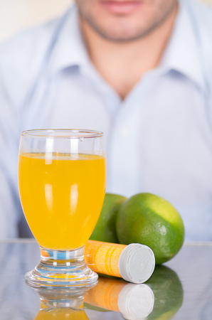 Handsome guy behind of Lemon, pills of vitamin C and a glass of vitamin C dissolved over the table