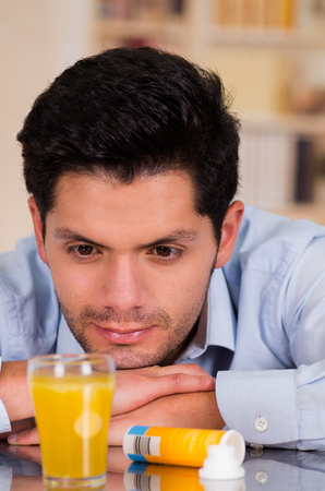 Handsome man watching the effervescent tablet in glass of water