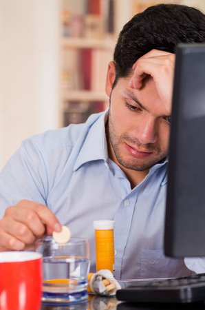 effervescence: Handsome bored man drooping a pill effervescent tablet in a glass of water in his office