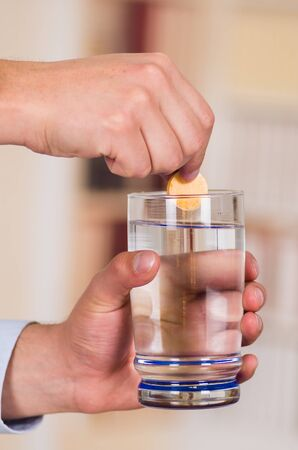 Man holding a pill effervescent tablet in his hand while he hold a glass of water in his other hand Stock Photo