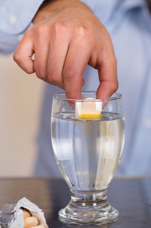 effervescence: Hand drooping a pill effervescent tablet in a glass of water