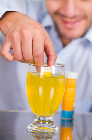 effervescence: Handsome smiling man drooping a pill effervescent tablet in a glass of water