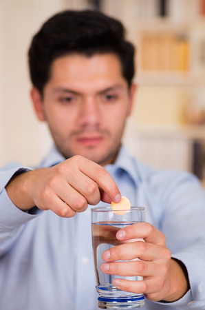 effervescence: Handsome man dropping effervescent tablet in glass of water