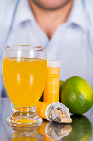 Lemon, pills of vitamin C and a glass of vitamin C dissolved over the table