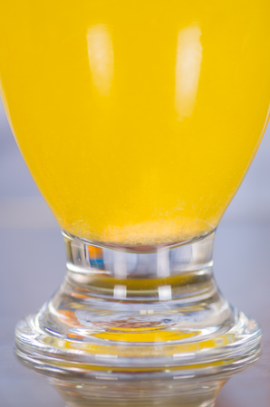Close up of a glass of vitamin C dissolved over the table