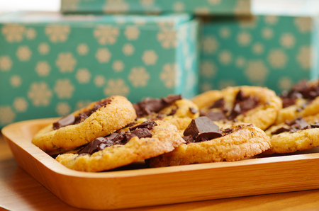 Delicious freshly baked cookies with chocolate on a wooden tray with a blurred background