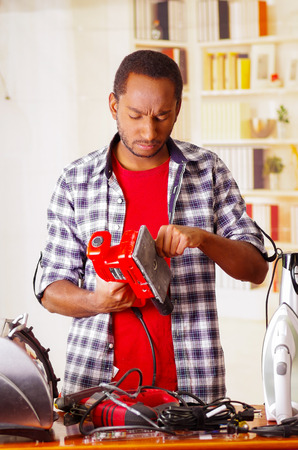 Mad Young African Ecuadorian male Technician fixing a red sander with his screwdriver on office background Stock Photo