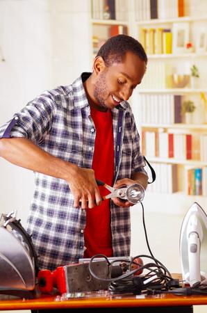 Happy Young African Ecuadorian male Technician repairing a machine using a Pliers