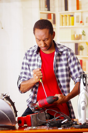 Young African Ecuadorian male Technician pucker his face while he is fixing a wood sander with a screwdriver