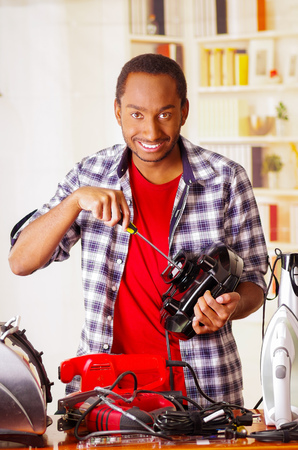 Happy Young African Ecuadorian smiling male Technician repairing a toaster with a screwdriver Stock Photo