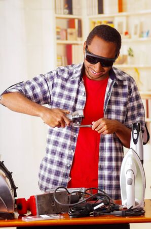 Happy Young African Ecuadorian male Technician wearing protection glasses and using a metal cutter with office background