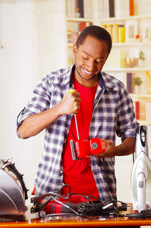 Happy Young African Ecuadorian male Technician fixing a red sander with his screwdriver on office background