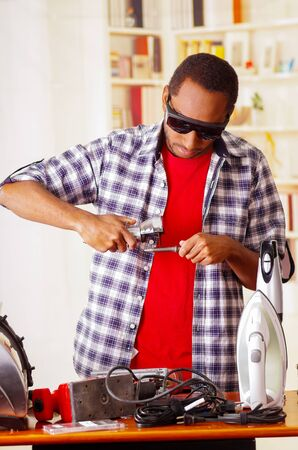 Young African Ecuadorian male Technician wearing protection glasses and using a metal cutter with office background Stock Photo