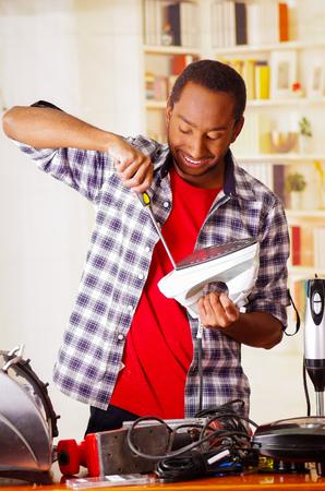 Happy Young African Ecuadorian male Technician repairing an iron with a screwdriver