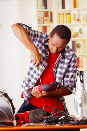 Young African Ecuadorian male Technician pucker his face having problems while he is fixing a wood sander with a screwdriver