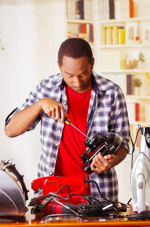 Young African Ecuadorian male Technician repairing a toaster with a screwdriver