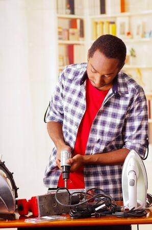 Young African Ecuadorian male Technician repairing a machine using a drill