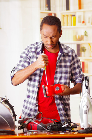Young African Ecuadorian male Technician pucker his face having problems while he is fixing a red sander with a screwdriver Stock Photo