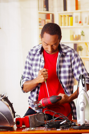 Young African Ecuadorian male Technician pucker his face having problems while he is fixing a red wood sander with a screwdriver