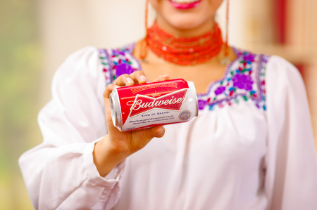 Quito, Ecuador - May 06, 2017: Smiling young woman wearing an indigenous clothes and pointing in from of her a refreshing Budweiser beer in a forest background
