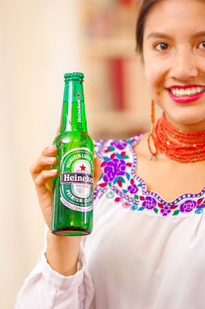 Quito, Ecuador - May 06, 2017: Close up of a beautiful smiling woman wearing an indigenous clothes while she is holding in her hands a bottle of Heineken beer in a forest background